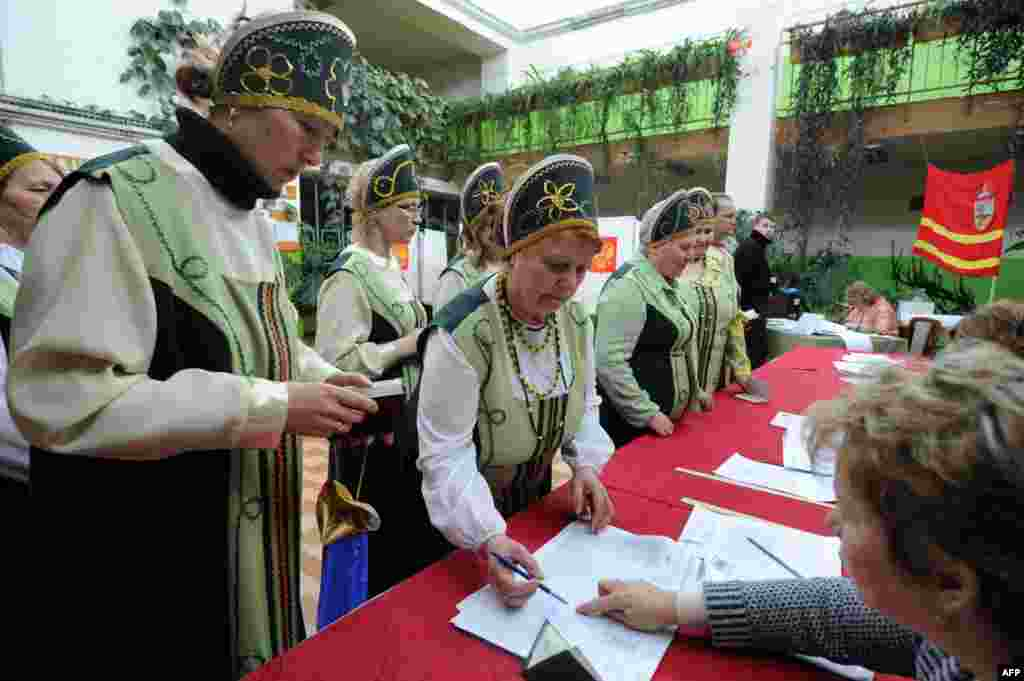 Wearing their traditional Russian costumes, members of a folk group receive ballots at a polling station in the village of Koshchino, outside Smolensk.
