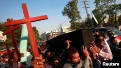 Members of the Pakistani Christian community carry wooden crosses and a casket during a demonstration to condemn the death of a Christian couple (file photo).