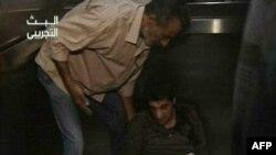 Мужчина помогает коллеге встать после взрыва на сирийском телевидении. 6 августа 2012 года.