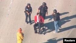 Полицейские сопровождают пострадавшего во время стрельбы в аэропорту мужчину к машине скорой помощи. Лос-Анджелес, 1 ноября 2013 года.