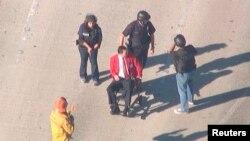 Полицейлер әуежайдағы оқиғадан зардап шеккен адамды жедел жәрдем көлігіне апара жатыр. Лос-Анджелес, АҚШ, 1 қараша 2013 жыл.