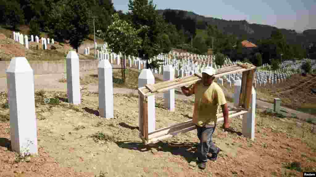 A worker on July 7 prepares graves for a ceremony at the Srebrenica memorial center in Potocari. The International Commission for Missing Persons has so far identified more than 7,000 Srebrenica victims.
