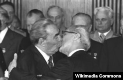 The Kazakh poster is a takeoff of the famous kiss between Soviet leader Leonid Brezhnev (left) and East German leader Erich Honecker.