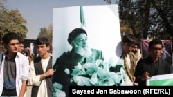 Afghanistan -- Afghan men carry a banner featuring slain head of Afghanistan's High Peace Council and former president Burhanuddin Rabbani during a gathering to remember him after a suicide attack in Kabul on September 21, 2011.