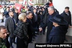 Прэзыдэнт Польшчы Анджэй Дуда (зьлева) цісьне руку прэзыдэнту Літвы Гітанасу Наўседу