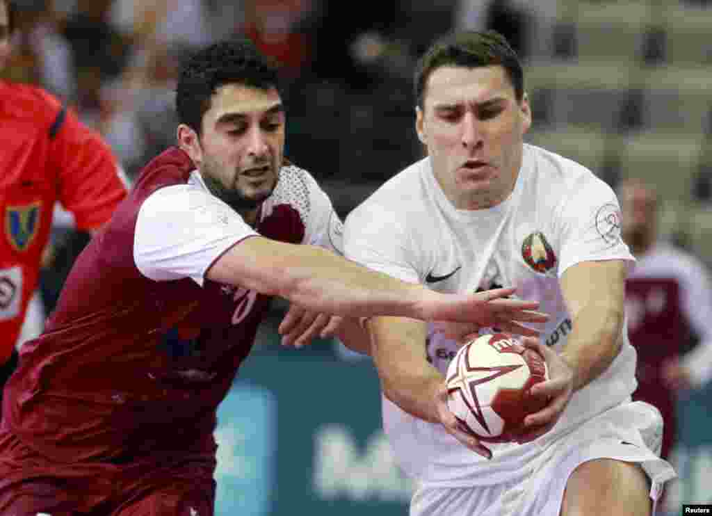 Abdulla Al-Karbi of Qatar and Barys Pukhouski of Belarus (right) run for the ball during their preliminary round of the 24th men's handball world championship in Doha. (Reuters/Mohammed Dabbous)