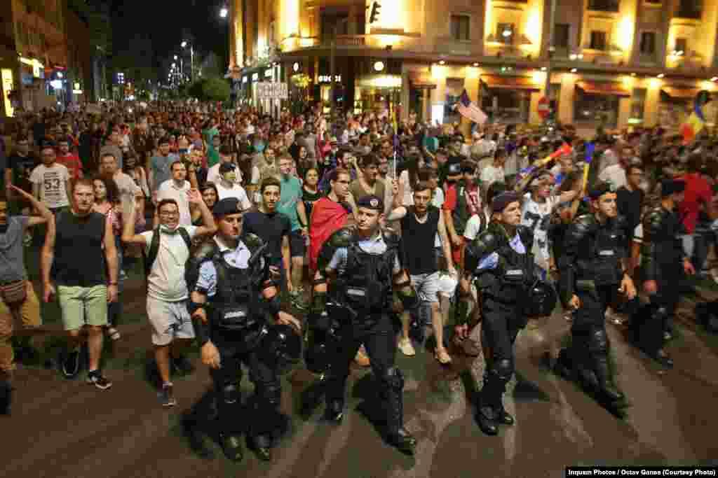 Протестующие маршируют по центру Бухареста 12 августа, третий день антиправительственных демонстраций