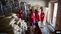 International Committee of the Red Cross workers enter a storehouse to check products after a Ukrainian convoy delivered humanitarian aid for eastern Ukrainian regions, in the town of Starobilsk, in August 2014.