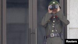 Севернокорејски војник ја набљудува границата со Јужна Кореја.