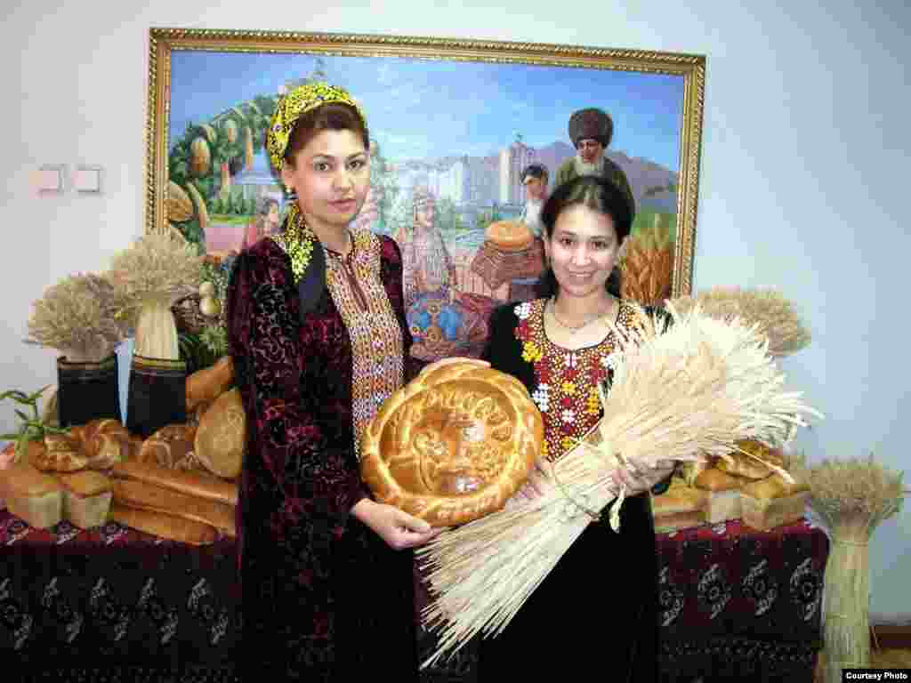 Turkmen women dressed in traditional dresses standing in front of typically decorated Norouz table with special Norouz bread - Noruz08