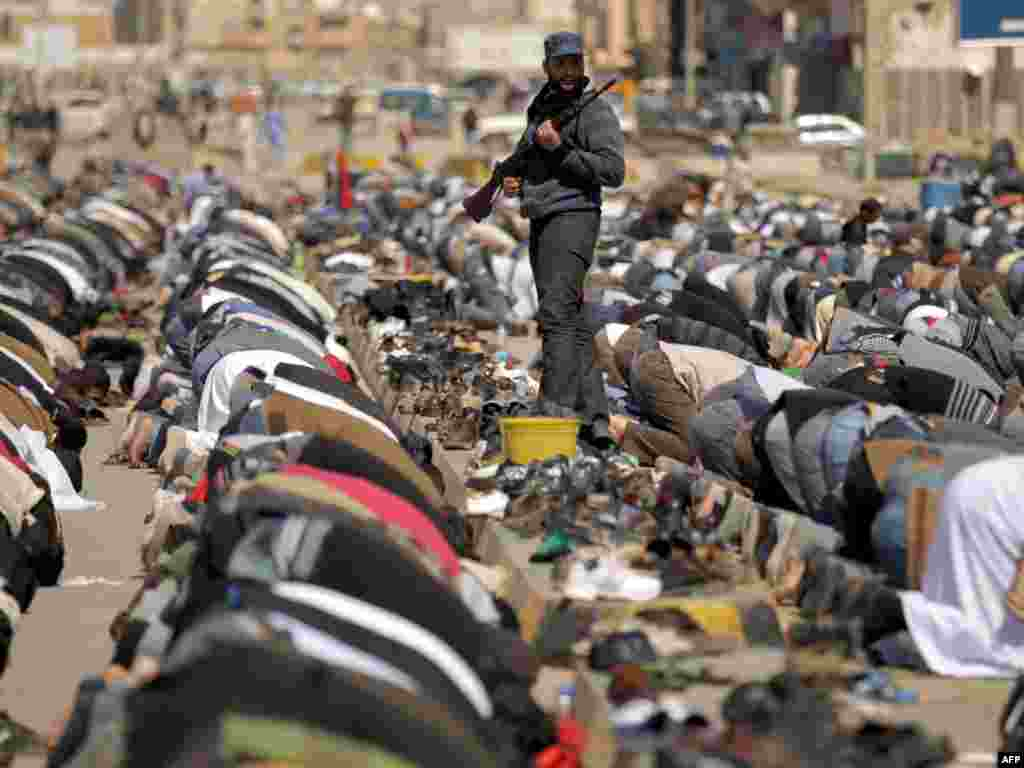 A Libyan rebel guards worshipers performing the Friday Noon Prayer in BenghaziPhoto by Patrick Baz for AFP