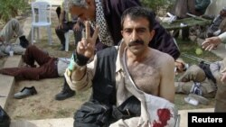 A camp resident gives the victory sign after clashes with Iraqi security forces at Camp Ashraf on April 8.