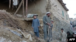 Pakistani residents gather next to the rubble of damaged house following an earthquake in Bajaur on October 26.