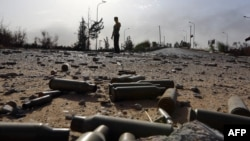 Spent bullet shells litter the ground as a member of the Islamist-linked militia of Misurata walks past following three days of battles in the area of Tripoli's international airport on August 21.