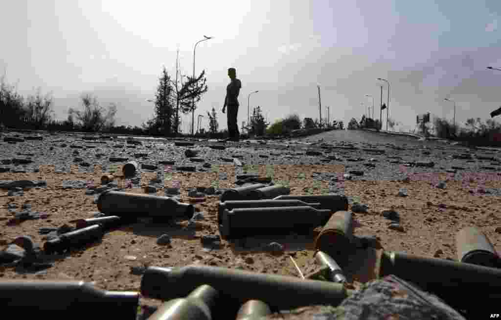 Spent bullet shells litter the ground as a member of the Islamist-linked militia of Misurata walks past following three days of battles in the area of Tripoli's international airport on August 21. (AFP/Mahmud Turkia)