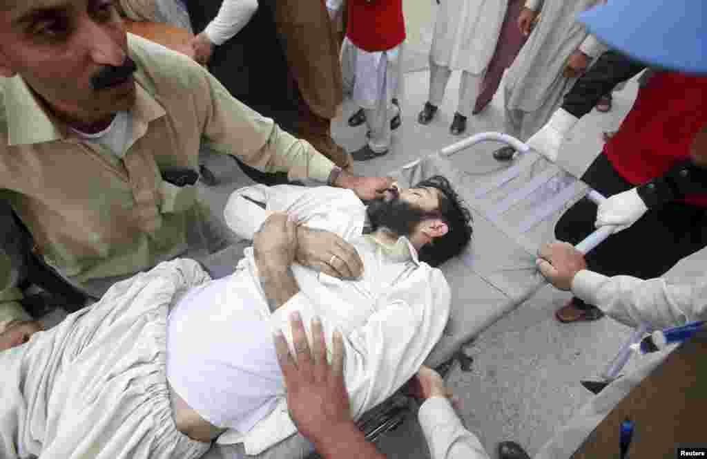 Rescue workers move an injured man at the Lady Reading Hospital in Peshawar, Pakistan.