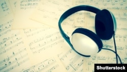 Czech republic. Headphone on music sheet sepia processed. Melody. Shutterstock.