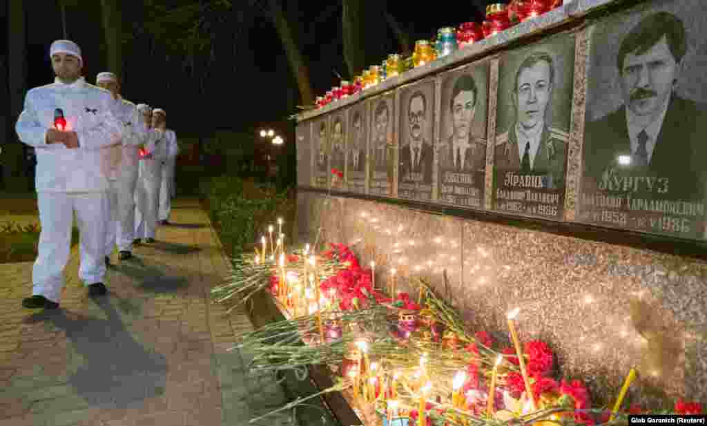 People carry candles in the Ukrainian city of Slavutych on April 26 at a memorial dedicated to firefighters and workers who died as a result of the 1986 Chornobyl nuclear disaster.