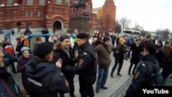"Moscow police detain Russians holding ""invisible placards"" of protest near the Kremlin on April 6."