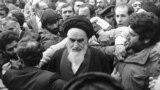 აიათოლა რუჰოლა ხომეინი, ირანის გადასახლებაში მყოფი რელიგიური ლიდერი, პარიზში დილის ლოცვის შემდეგ, პრესკონფერენციას მართავს. მთარგმნელის მეშვეობით, მან საერთაშორისო ჟურნალისტებს უთხრა, რომ ირანის არმიის მიერ აეროპორტების დახურვის გამო, თეირანში ჩასვლის გადადება უწევს. 25 იანვარი, 1979.