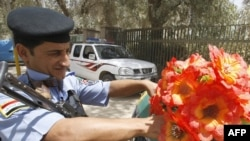 A police officer in Baghdad affixes plastic flowers to the front of a police car as the nation prepares for the official withdrawal of U.S. troops from cities and towns.