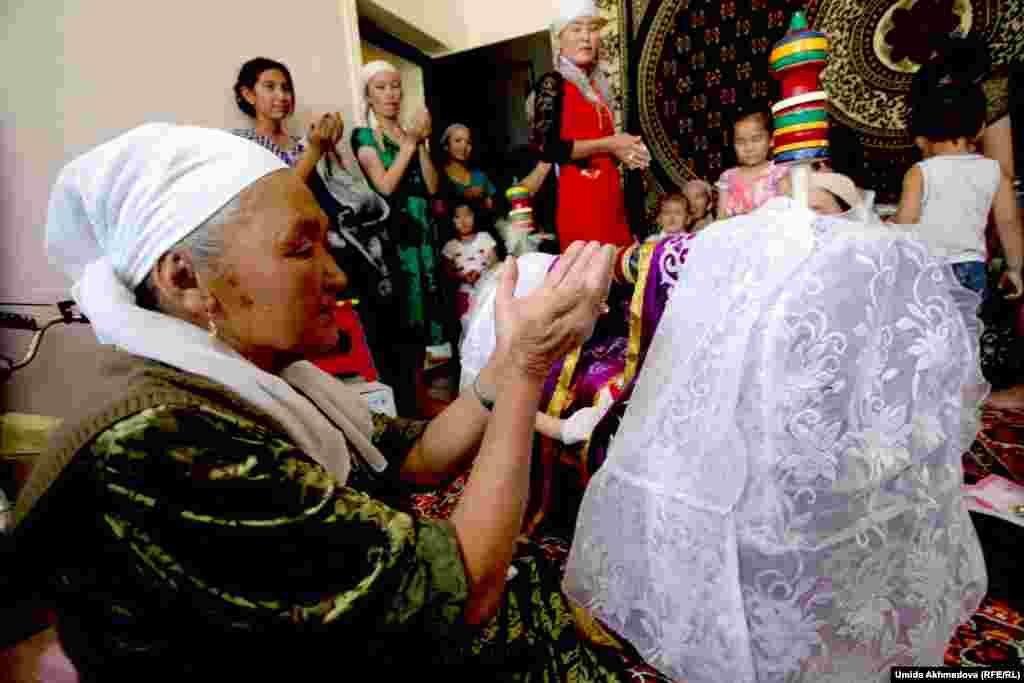 After Darkhan is put in the cradle, the women pray, with the boy's grandmother reading a prayer.