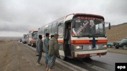 Afghan policemen check buses near Ghazni on March 24.