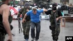 """Бойцы батальона """"Восток"""" ведут пророссийского активиста, захваченного ими после штурма здания областной администрации в Донецке. 29 мая 2014 года."""