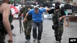 Донецк қаласындағы облыстық әкімдікті басып алған «Восток» батальонының жауынгерлері ресейшіл белсендіні ұстап әкетіп барады. 29 мамыр 2014 жыл.