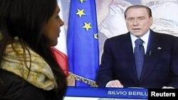 Женщина следит за телевыступлением экс-премьера Италии Сильвио Берлускони, 13 ноября 2011