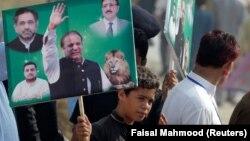 Исламабадта сот алдында Наваз Шарифті қолдап, оның суреті басылған плакат ұстап тұрған адам. Пәкістан, 26 қыркүйек 2017 жыл.
