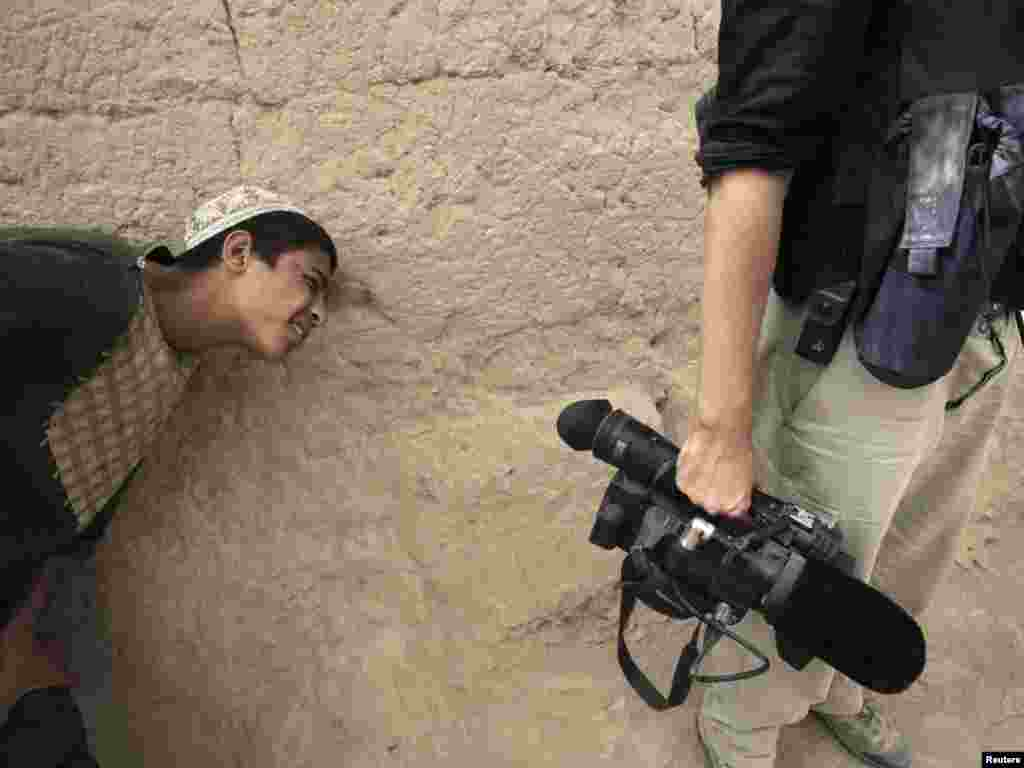 An Afghan boy tries to get a peek through the viewfinder of a journalist's video camera in the village of Saidon Kalacheh, north of Kandahar, on July 28. Photo by Bob Strong for Reuters