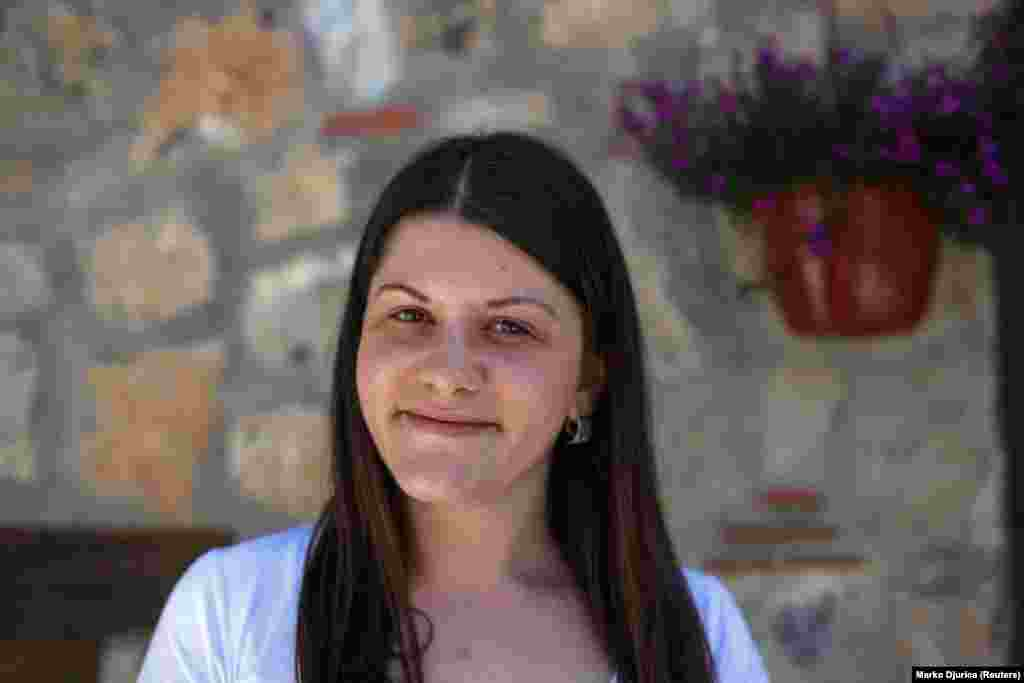 "Emilija, a hotel receptionist, poses for a portrait in an old part of the waterside city of Ohrid. Emilija says she expects living standards to rise once the country joins the EU and NATO. ""Greeks come here as tourists and we're friends,"" she says. ""I can say only good things about them. It is only politics that is causing trouble between people."""