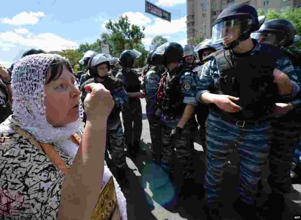 An Orthodox adherent remonstrates with police as she and others protest against the gay-rights march.