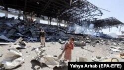 Дівчинка й повстанець Хуті в Ємені на місці, куди влучила ракета, ймовірно, випущена силами коаліції на чолі з Саудівською Аравією