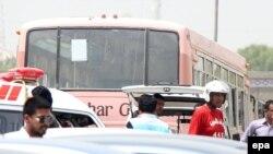 Сотрудники пакистанских спасательных служб на месте нападения вооруженных людей на автобус. Карачи, 13 мая 2015 года.