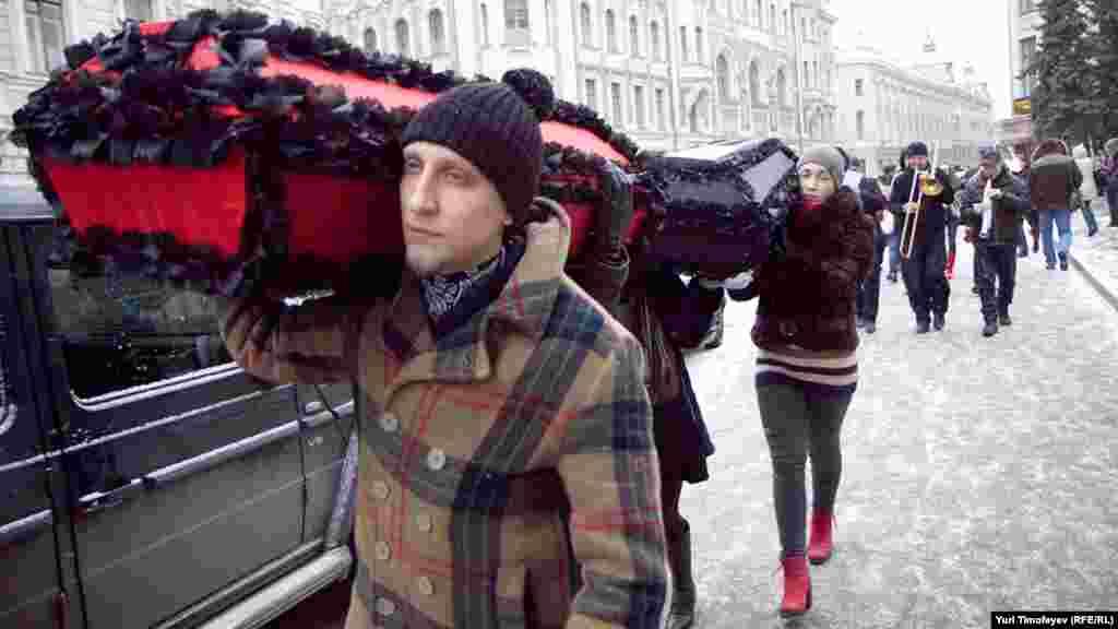 """Траурная процессия прошла по улице Ильинка: несколько человек несли гробы с надписями """"Профилактика"""" и """"Лечение"""", оркестр играл траурный марш."""