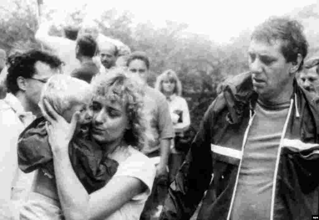 An East German woman hugs her crying child as they are reunited after being separated during the rush across the border into Austria on August 19.