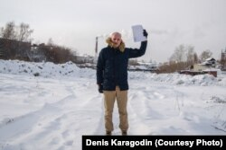 Denis Karagodin, holding the document showing who killed his great-grandfather, stands at the place where he believes he is buried in a mass grave along with some 15,000 other victims of the Great Terror.