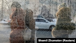 People wait at a bus stop on a cold day in Almaty.