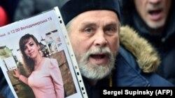 Учасник акції протесту біля Головного управління поліції Київської області тримає фото вбитої юристки Ірини Ноздровської. Київ, 2 січня 2018 року