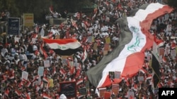 Thousands of Iraqis, waving national flags, take to the streets in central Baghdad on January 24.