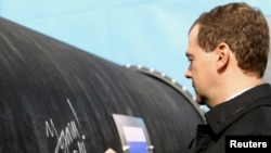 Russian President Dmitry Medvedev writes 'Good Luck!' on a section of the Nord Stream pipeline.