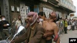 Йемендіктер шеруде жараланған адамды ауруханаға апара жатыр. 18 қыркүйек, 2011