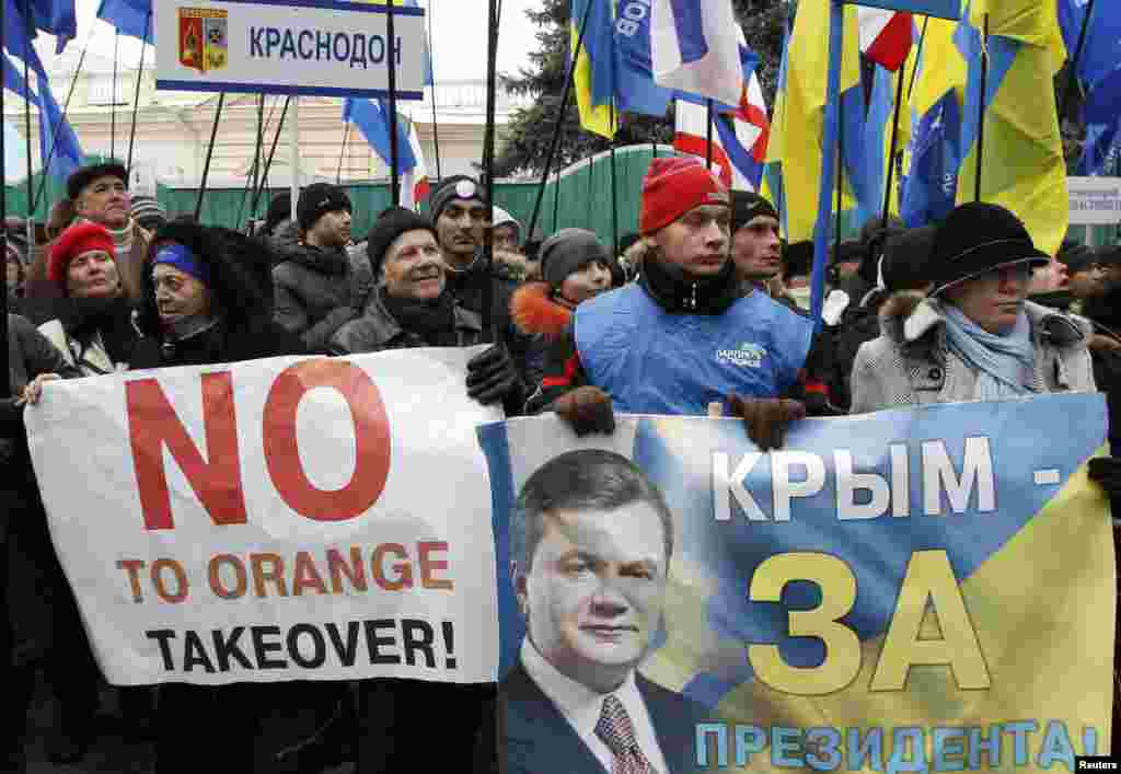 Supporters of Ukranian President Viktor Yanukovych hold flags and placards.
