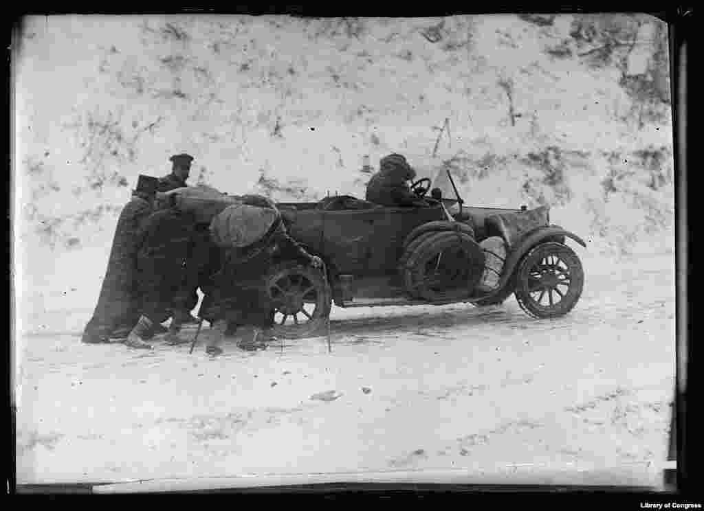 This picture shows the trials of an American Red Cross car that made the trip from Bucharest, Romania, across Bulgaria, to Pirot, Serbia, in November 1919 before the railroad was reconstructed. It was so cold the engine wouldn't work properly. Peasants helped push it uphill and it coasted down.