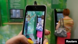 A Russian woman plays Pokemon Go while someone uses an ATM in Krasnoyarsk, Russia.