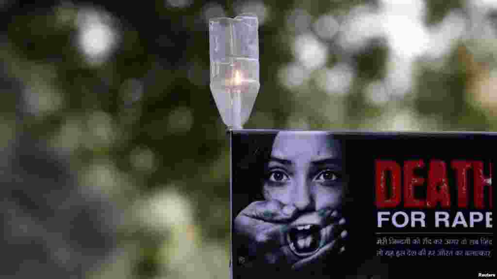 A candle is seen on a placard during a protest in New Delhi over the death of a woman who was gang-raped on a bus. (Reuters/Adnan Abidi)