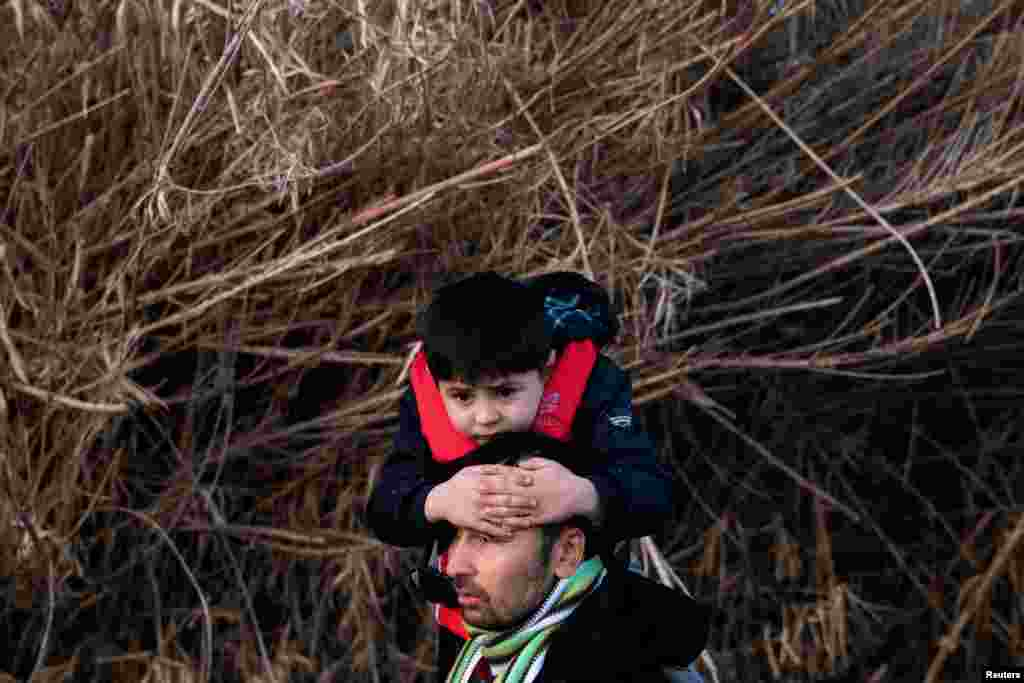 An Afghan man carries his son after arriving on the island of Lesbos.Under a 2016 agreement with the European Union, Turkey had restricted migration flows from Syria and other countries to Europe.
