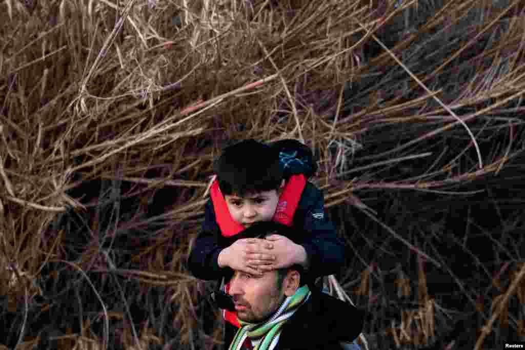 Afganistanac nosi svog sina nakon što je stigao na ostrvo Lesbos. Prema sporazumu s Europskom unijom iz 2016. godine, Turska je ograničila migracijske tokove iz Sirije i drugih zemalja u Evropu.